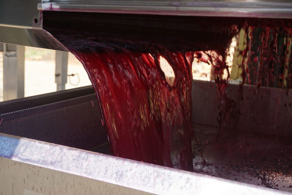 Red wine pouring from machine.