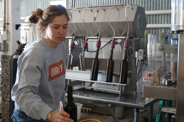 Sofia moving wine from filler to corker.