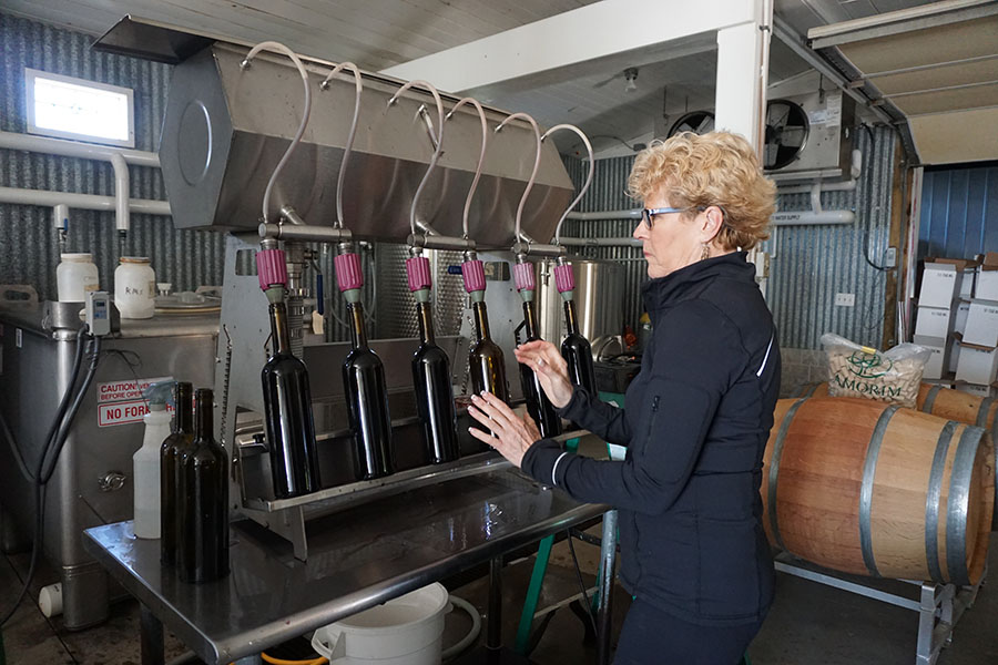 Woman using a machine to fill bottles of wine.