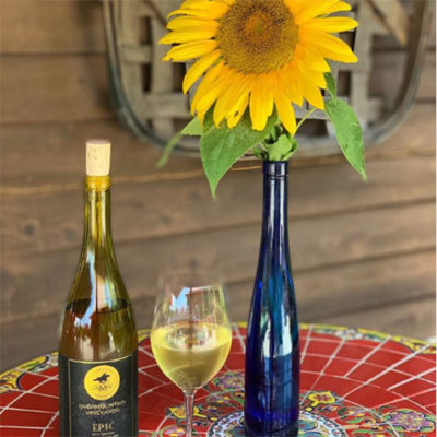 Bottle and glass of wine with sunflower in blue bottle.